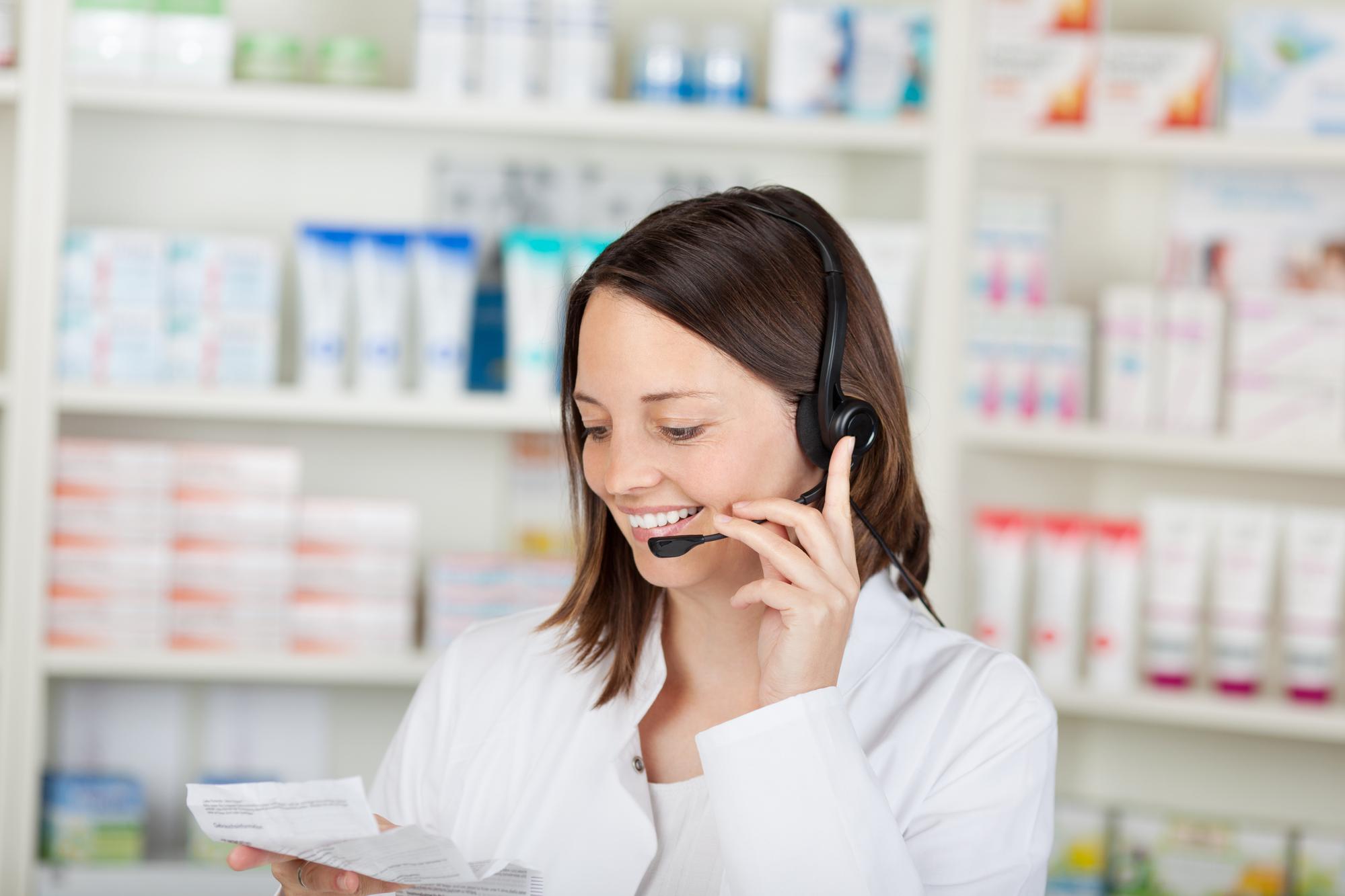 Happy mid adult female pharmacist conversing on headset in pharmacy